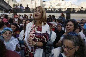 אישה עם טלית מובילה תפילה בכותל
