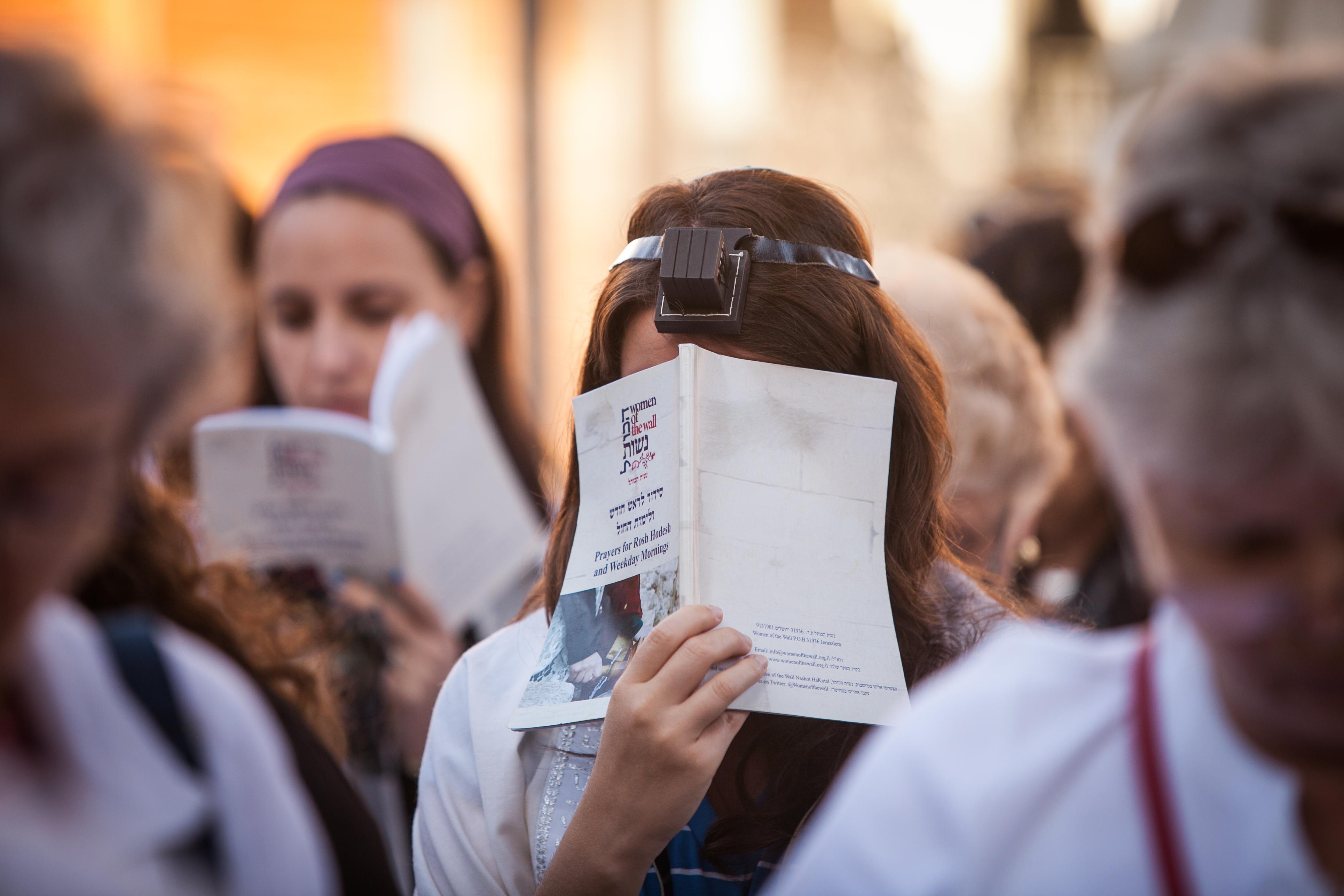 אשה עם תפילין וסידור נשות הכותל מתפללת