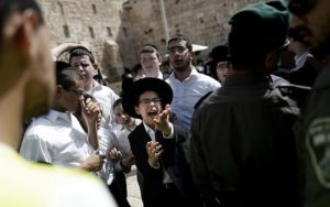 A group of Jewish ultra-Orthodox men and boys oppose the prayer service of the Women of the Wall