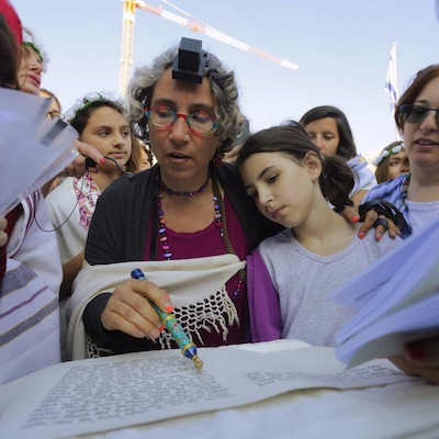 Mother and daughter reading from the torah
